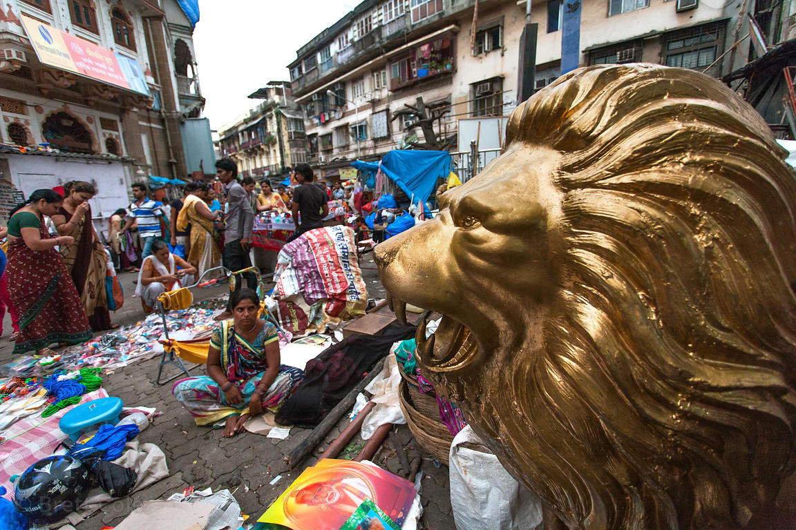 A golden lion statue at a busy market intersection, Buleshwar, Mumbai, India