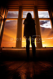 An atmospheric image of the silhouette of a girl standing, looking out of a large window, at the sunrise / sunset.