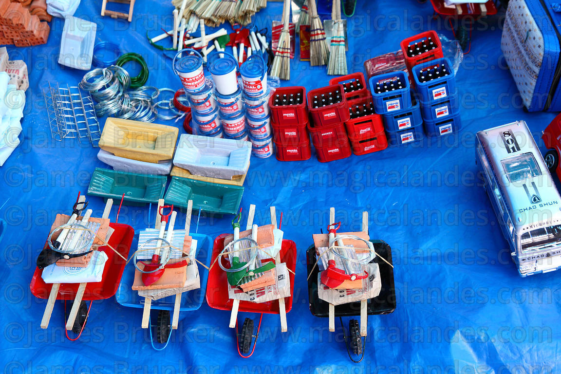Miniature wheelbarrows with construction materials for sale on market stall, Alasitas festival, La Paz, Bolivia