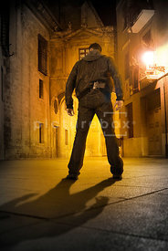 An atmospheric image of a mystery man with a gun standing in an old street lit by streetlights.