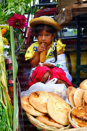 Girl with typical local bread loaves in back of a pick up truck during Carnival parades, San Lorenzo, Tarija Department, Bolivia