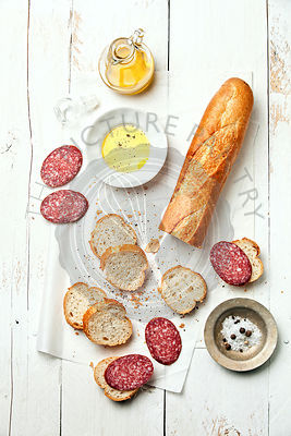 Baguette with sausage on white wooden background