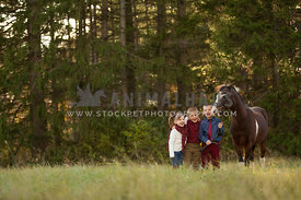 children laughing standing with pony in forest