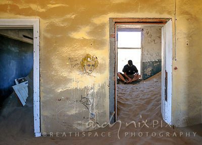 Man sitting in an empty, decaying building in an abandoned Victorian desert ghost town.