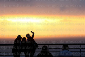 Girl taking selfie with friends at sunset, Larcomar, Miraflores, Lima, Peru