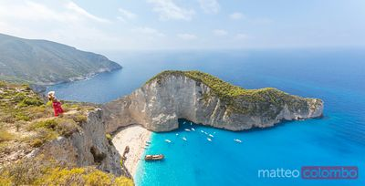 Woman standing over famous Navagio beach. Zakynthos, Greek Islands, Greece