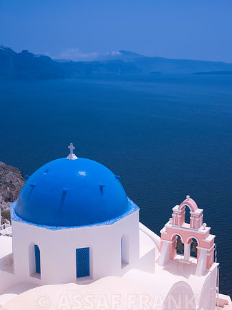 A church dome on a cliff above the sea in the Greek Isle of Santorini.