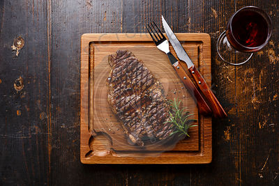 Grilled Steak Striploin and red wine on cutting board on dark wooden background