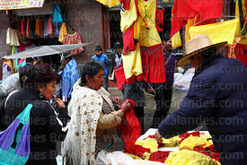 Aymara woman shopping for red and yellow underwear on New Year's Eve, La Paz, Bolivia