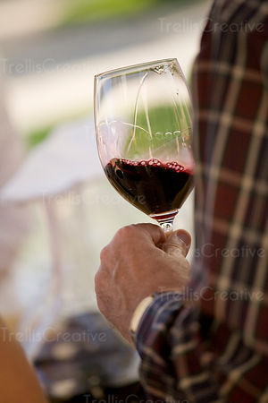 A man swirls a glass of red wine