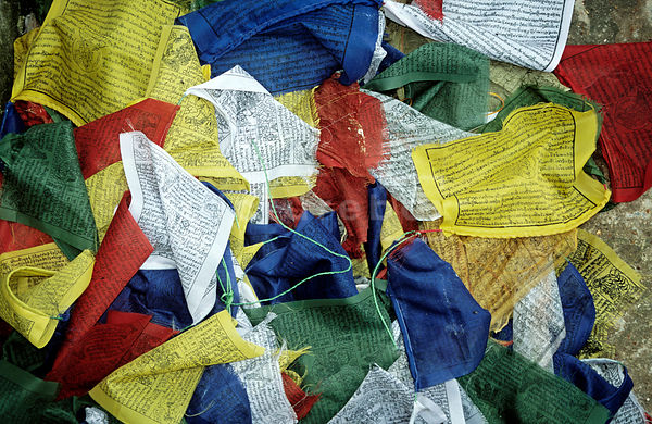 A colourful landscape image of red, yellow, green and blue prayer flags on the ground in Nepal.