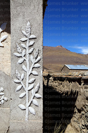 Detail of quinoa plant designs on facade of rustic church in Churacari village, Bolivia