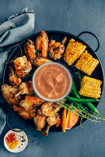 Grilled chicken wings are served on a black tray accompanied by grilled corn, green peppers, fresh thyme, peach slices and a ...