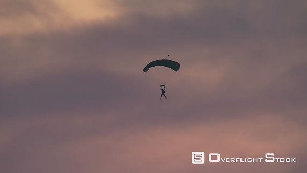 Air-to-air view of sunset-silhouetted skydiver