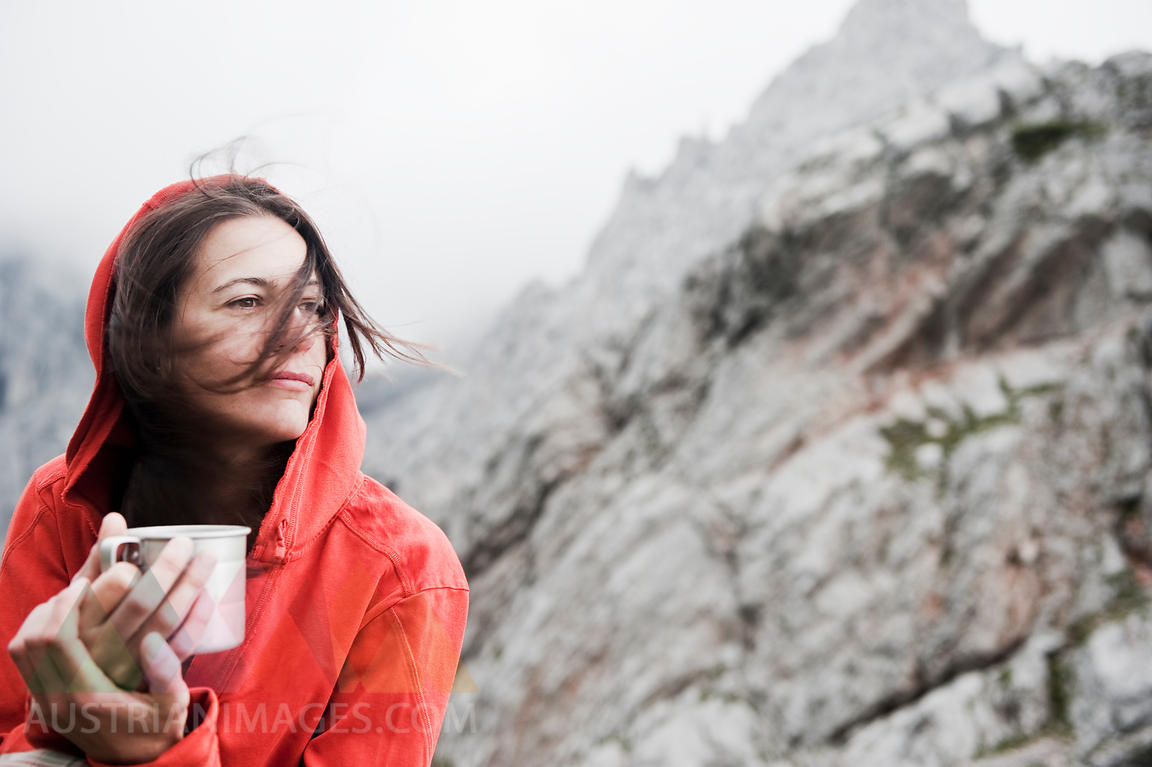 Austria, Salzburg Country, Filzmoos, Woman holding cup sitting on mountain