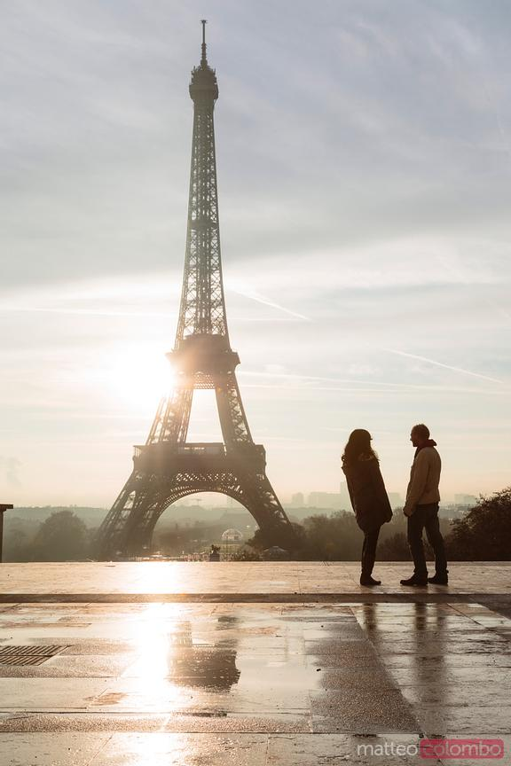 Couple looking at Eiffel tower at sunrise, Paris, France