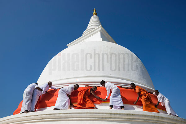 Buddhist Monks Wrapping the Colours of the Buddhist Flag around Thuparama Dagoba during Full Moon Poya Day