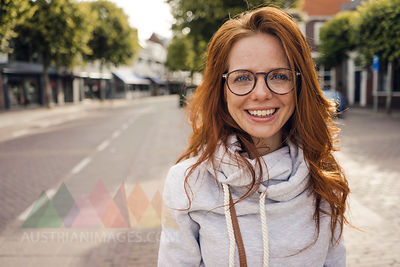 Redheaded woman with headphones in the city
