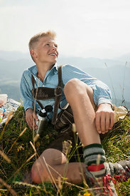 Germany, Bavaria, Boy in traditional clothing taking a rest in mountains