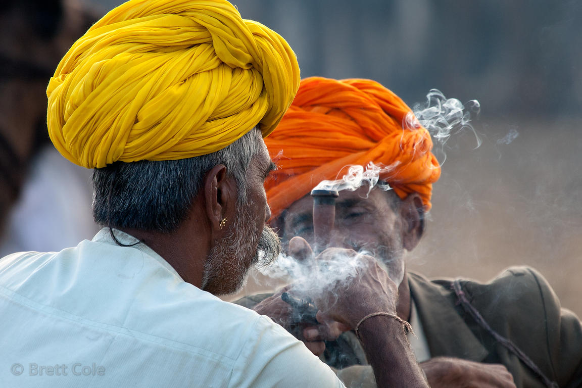 Men smoking a chillum of tobacco or opium during the Pushkar camel fair 2010, Rajasthan, India