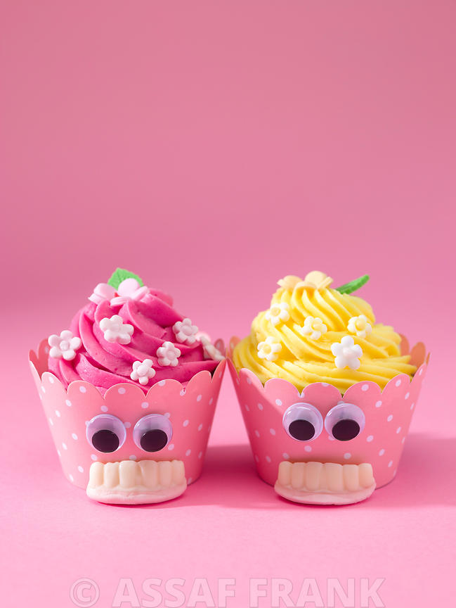 Cupcakes with false teeth on pink background