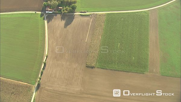 Flying over farm machines at work in a wide field, Belgium