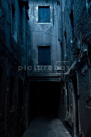 An atmospheric image of a dark narrow derelict street in Venice, Italy.