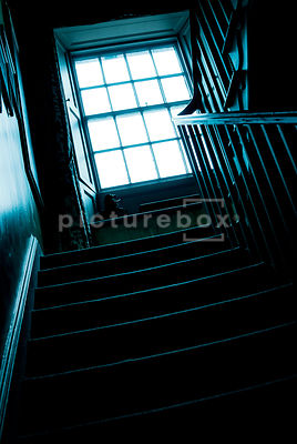 An atmospheric image of the light coming through an old window, into an Victorian stairwell.