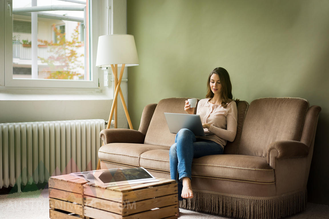 Young woman sitting on couch with cup of coffee using laptop