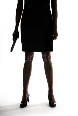 A crop of a silhouette of a woman standing with a gun – shot from mid level.