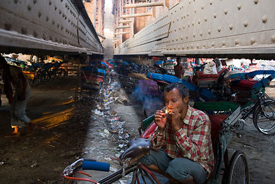 India - New Delhi - A homeless cycle rickshaw driver smokes underneath a bridge at a parking lot next to the Yamuna River whe...