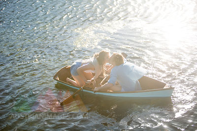 Young couple kissing in a rowing boat on a lake