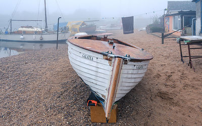Misty scene with old boats on the shoreline near the boatyard and sailmaker on a creek in Exmouth, Devon, UK