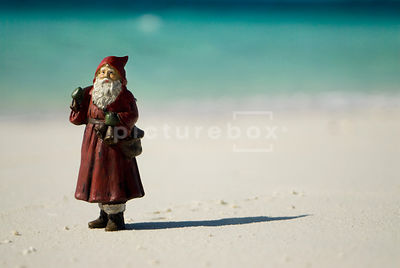 An image of a Santa Claus Christmas decoration standing on a sandy beach.