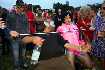 UK - Standon - Men dance and limbo beneath a stick at the Standon Calling Festival
