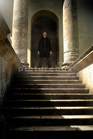 An atmospheric image of a mystery man standing at the top of some steps, looking out from an old temple.