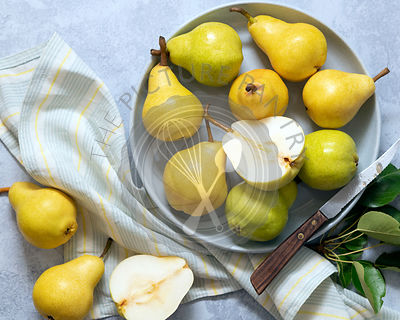 Yellow and green pears in a bowl with a pear cut in halves.