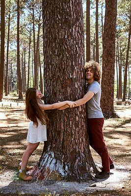 Happy young couple hugging a tree in forest