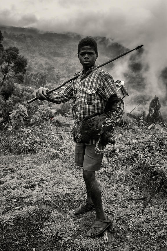 Young Man Carrying Chicken and Spear