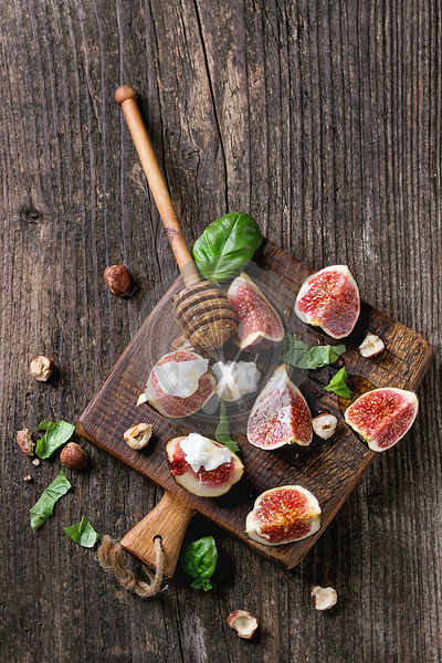 Fresh sliced figs with ricotta cheese, basil leaves, hazelnut and honey from honey dipper