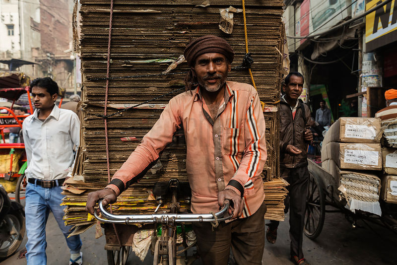 Portrait of a Man Carrying Cardboard on a Bicycle