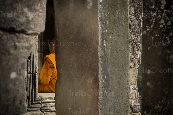 A young monk sits among the ruins of Angkor Wat in Cambodia