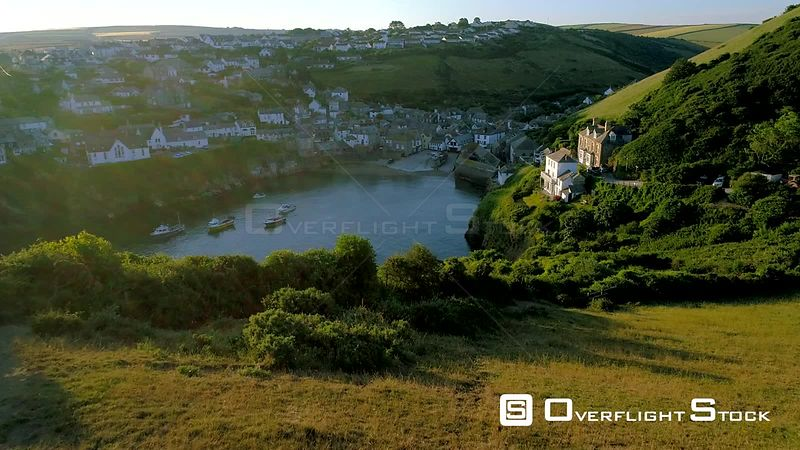 Drone flies over cliffs to reveal village of Port Isaac in Cornwall during the early morning light