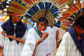 Young female machetero dancer eating an ice cream during main procession of festival, San Ignacio de Moxos, Bolivia