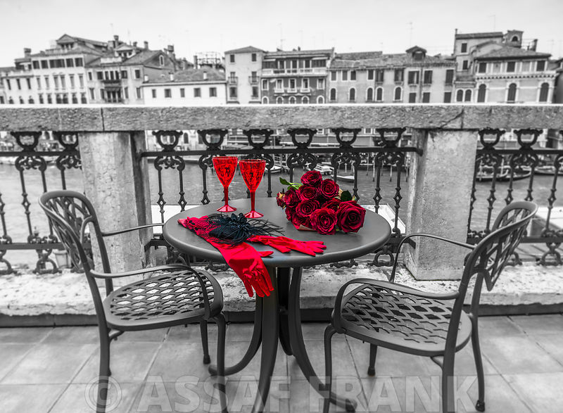 Bunch of Roses with wine glasses and female hand gloves on cafe table, Venice, Italy