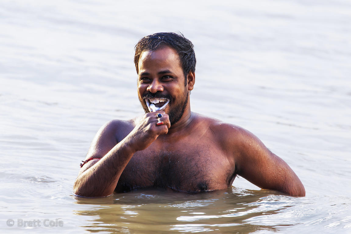 A man brushes his teeth in the not very clean Hooghly River (also known as the Ganges), Sovabazar Ghat, Kolkata, India