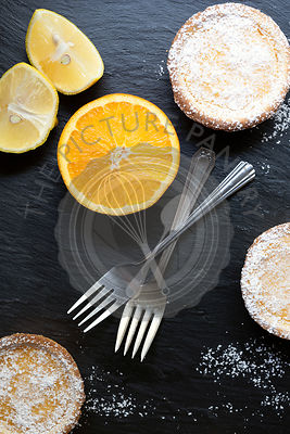 Lemon tarts dusted with powdered sugar, two forks, half an orange and lemon pieces.