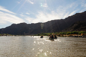 A group of canoeists paddling on a river flowing below mountains in the desert, sunlight sparkling on water, backlt