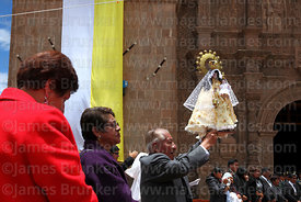 Devotee holds up his statue of Virgen de la Candelaria in front of the cathedral after central mass, Puno, Peru