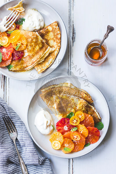 Crepes with a citrus fruit side.